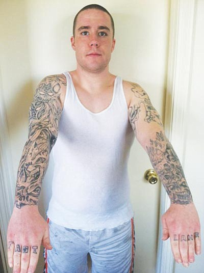 Curtis Standlee/Courtesy<br> Curtis Standlee, who was arrested on armed robbery charges last summer, displays his tattoos. The suspect in the armed robbery was described as having a possible tattoo on his right upper arm. Standlee said it would have been hard for witnesses to miss his two full-sleeves of tattoos as well as the writing on his knuckles.
