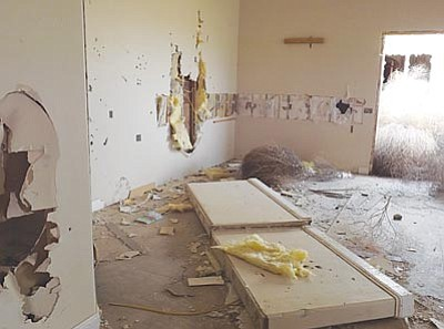 AHRON SHERMAN/Miner<br> Here is a room in one of the homes on Eagle View Road. The damage – holes in the wall and an overturned banister – is typical.