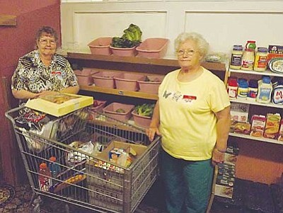 AHRON SHERMAN/Miner<br /><br /><!-- 1upcrlf2 -->Kingman Area Food Bank Executive Director Betty Kahlor along with one of her employees, Mary Winchester, stand with a freshly made food basket for a family of three.<br /><br /><!-- 1upcrlf2 -->