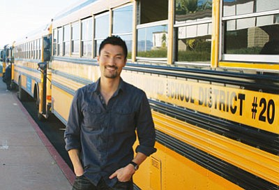 "Courtesy<br /><br /><!-- 1upcrlf2 -->Host of PBS's ""America Revealed"" Yul Kwon stands in front of a row of KUSD buses."