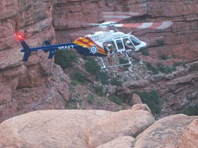 MCSO/Courtesy<br> The Kingman Ranger and Arizona Department of Public Safety helicopter lowers a Mohave County Sheriff's Office Search and Rescue member to pull an injured hiker from the North Rim of the Grand Canyon Sunday.