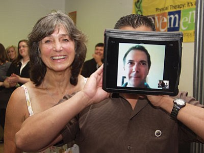 Courtesy<br> John LaDouceur (right), who was on vacation in Hawaii, celebrates with the help of an iPad after receiving his pin from PTA Program Director Joelle Grossman.