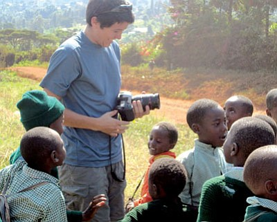 "The Roots of Happiness/Courtesy<br /><br /><!-- 1upcrlf2 -->Ryan Abella, a Kingman High grad and videographer, stands in the midst of a bunch of children from the Tumaini Children's Home in Nyeri, Kenya, while filming ""The Roots of Happiness."" The film crew is hoping to sell the film and use the funds to send some of the children to college."