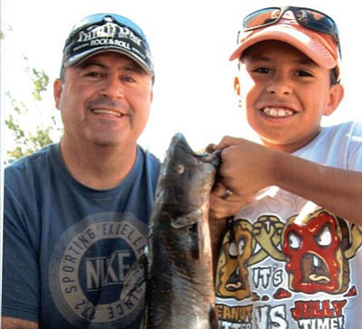 Don Martin/Courtesy<br /><br /><!-- 1upcrlf2 -->Bo Sena (left) and his 7-year-old son Kyle, show the 4.3 pounds catfish that Kyle caught at the Fishing For Smiles event.