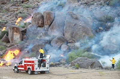 JC AMBERLYN/Miner<br> Firefighters battle a blaze on rugged terrain north of Kingman near sunset Thursday. Authorities believe the fire was caused by a person.