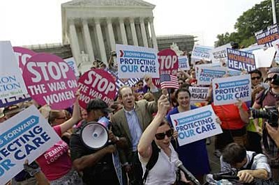 David Goldman/AP Photo<br>Supporters of President Barack Obama's health care law celebrate outside the Supreme Court in Washington Thursday after the court's ruling.