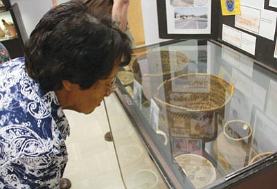 JC AMBERLYN/Miner<br>  Marilyn Bravo of the Hualapai Tribe looks at some baskets on display that her grandmother had woven.