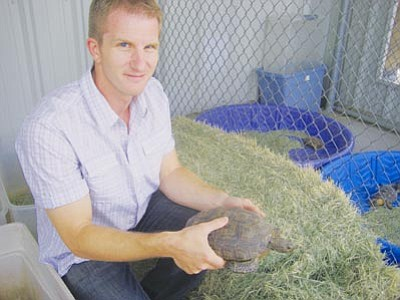 ERIN TAYLOR/Miner<br> Arizona Game and Fish Non-game Specialist John Kraft holds one of the desert tortoises that will be available for adoption from 11 a.m. to 3 p.m. Saturday at the Kingman library on Bank Street. The gentle desert creatures live anywhere from 50 to 100 years and can weigh up to 15 pounds.