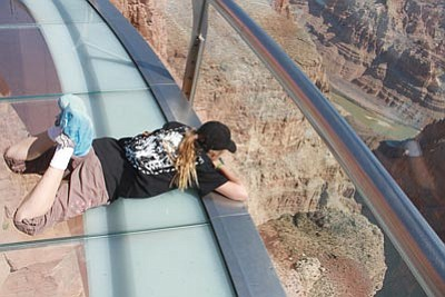 JC AMBERLYN/Miner<br> Drew Stephenson, 11, sprawls out on the Grand Canyon Skywalk in April to take in the view thousands of feet below.