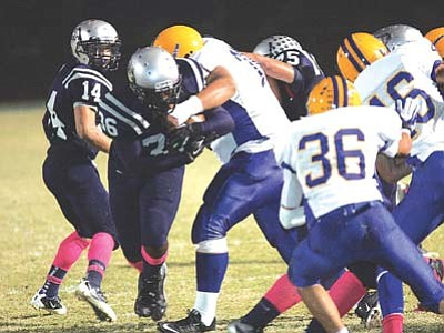 RODNEY HAAS/Miner<br> Kingman High's Cristian Gutierrez gets a hand on Willow Canyon's Deon Goodwin during the Bulldogs' 21-6 loss Friday night in Surprise.