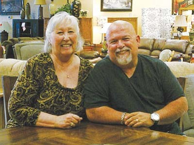 Courtesy<br> Mary and Gary Christopher at Home Style Furniture's new location. The store may be new, but the Coats 4 Kids Drive they run is not.