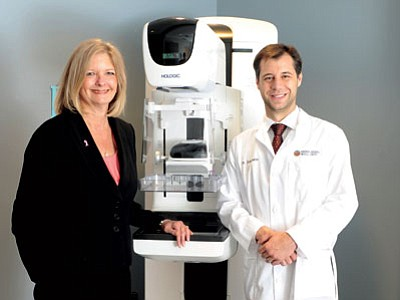 HOLOGIC/Courtesy<br> Teri Williams, left, and Dr. Christopher Johansen stand with KRMC's tomosynthesis breast imaging machine, which diagnosed Williams with a breast tumor in late September. Williams and Johansen are partners in a program that provides low-cost or free mammograms for uninsured or underinsured women.