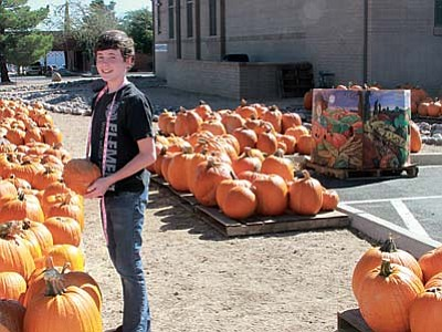 JC AMBERLYN/Miner<br> Joseph Collins, 13, was happy to help sell pumpkins for the youth group Saturday.