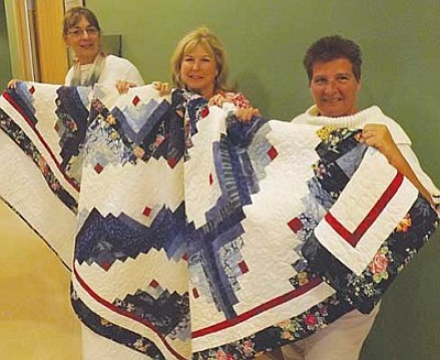 AHRON SHERMAN/Miner<br /><br /><!-- 1upcrlf2 -->From left, Fit at Fifty Program Coordinator Terri Holloway, North Country HealthCare Community Outreach Coordinator Ruffin Waldron and Referral Specialist Annette Seyssens show off a quilt which is being raffled off to help fund the Fit at Fifty program.