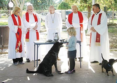 JC AMBERLYN/Miner<br> From left to right, Pastor Pam Wagner (St. John's), Fr. Philip Shaw (Trinity), Ben Rodenbeck (Trinity), Pastor Ray Christiansen (Grace Lutheran) and Fr. Leonard Walker (Divine Savior) say a prayer Saturday. Gabrielle Rodenbeck, 4, stands in front with her dog Dinkus.