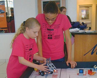 Courtesy<br> Robo Wranglers Rebecca Leggett and Chelsea Heitman of the Kingman Academy of Learning worked on their team's contraption last week during a FIRST Lego League scrimmage in Kingman.