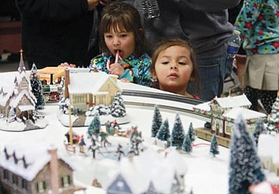 "JC AMBERLYN/Miner<br> Julyssa Pesqueira (left), 6, and Ana Lyssa Pesqueira, 3, look at a winter ""village"" and toy trains in motion at the Railroad Museum's display Saturday."