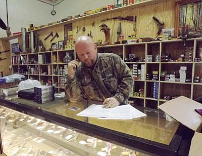 AHRON SHERMAN/Miner<br> Chris Wagner works through a stack of background check applications Friday at his store, The Gun Shop.