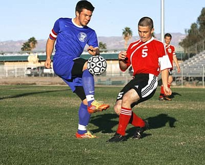 RODNEY HAAS/Miner<br> Kingman High senior Darin Kamin looks to advance the ball during a match earlier this year. Professional soccer player Hormoz Tabrizi will be teaching different skills when the Bulldogs soccer teams host a soccer camp for boys and girls begining Friday at Kingman High School.