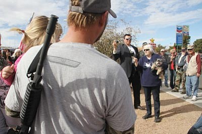 JC AMBERLYN/Miner<br> Scott Breen and his daughter Zoey, 2, (foreground) listen as Patricia K. Koch, holding her dog Max, speaks to the crowd during Friday's rally. She said that an intruder attempted to break into her home once but left when she warned him that she was armed. Luca Zanna stands to her left in the photo recording the event.