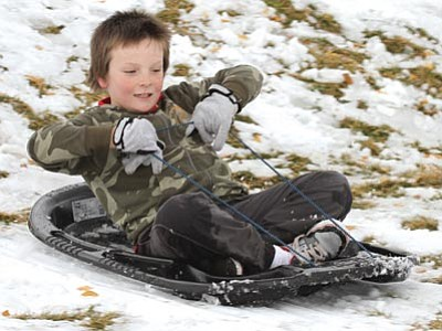 JC AMBERLYN/Miner<br> Kaleb Jordan, 8, slides down a hill near Eastern Street and Southern Avenue after snowfall earlier this month. Cold weather and precipitation – including the possibility of snow – are in the forecast starting tonight, with Wednesday expected to be wet and cold.