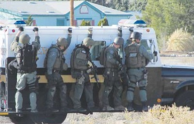 DOUG McMURDO/Miner<br /><br /><!-- 1upcrlf2 -->Members of the Mohave County Tactical Operations Unit approach the standoff scene Wednesday.