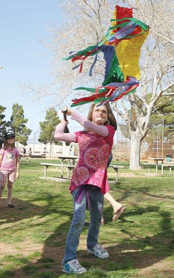 Trinity Wilton takes a swing at the piñata. Her mother, Coleen Root, can be seen walking behind her and Aryana Solomon, 7, watches at the left.<BR>JC AMBERLYN/Miner