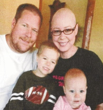 "Nicole ""Nikki"" Lane is facing advanced breast cancer. Here, the Kingman mom sits for a photograph with husband Jason, stepson Forrest and baby daughter Brooke.<BR>Courtesy"