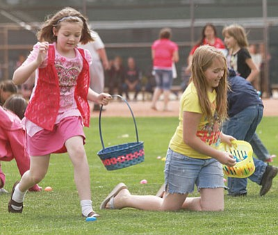 Addison Esser, 9 (left), and Kelley Montgomery, 11 grab eggs in the Age 9-11 field during the 2012 Easter Egg Hunt held at Centennial Park last year.<BR>JC AMBERLYN/Miner