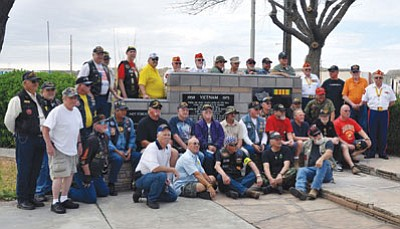 Many of the retired and former military personnel who attended the Vietnam Veterans Day ceremony and celebration pose by the Vietnam Memorial Wall at Locomotive Park Saturday in downtown Kingman. More than 100 people attended the ceremony, which included talks from Arizona State Representative Doris Goodale and Mohave County Supervisors Gary Watson and Joy Brotherton.<BR>BUTCH MERIWETHER/Courtesy