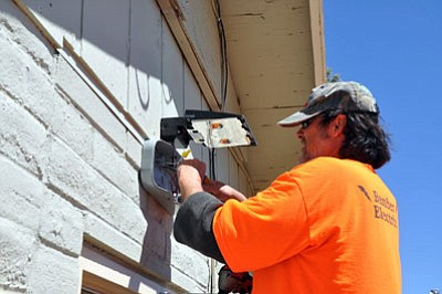 Scott Lederman, an electrician with Bamber Electric, installs new lights above one of the doors of a Mohave County-owned building at 950 Buchanan St. The $110,000 construction and renovation project that was approved by the Mohave County Board of Supervisors is nearing completion and will bring the facility into compliance with city codes and the American With Disabilities Act.<BR>BUTCH MERIWETHER/Courtesy