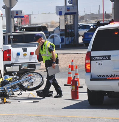 A Kingman Police officer looks over the scene of a fatal accident on Andy Devine Avenue north of I-40 Saturday morning.<BR>BUTCH MERIWETHER/Courtesy
