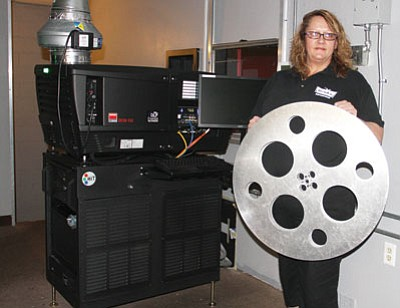General Manager Annette Post shows the difference between the old silver film reels used at Kingman Cinemas to run movies and the new digital cinema projector and server behind her that use a hard drive. Post said the digital system produces a clearer, brighter movie.<BR>JC AMBERLYN/Miner