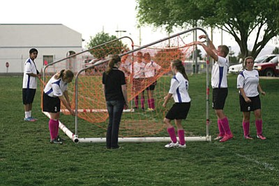 Members of the Kingman Academy soccer team take down nets for what could be the last time following their 2-1 loss to South Ridge Tuesday afternoon. With KAHS' move to the AIA, the soccer program will be suspended for at least the next two years. <BR>RODNEY HAAS/Miner