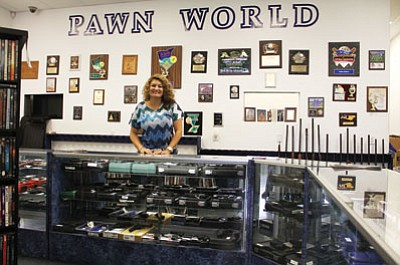 Rosalba Homer stands behind the counter at Pawn World at 201 E. Beale St. Tuesday.<BR>JC AMBERLYN/Miner