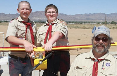 From left, Justin Lackey, 12, and Matthew Moses, 13, of the Boy Scouts and Charles Moses of the Kingman Modelers pose with one of the aircraft they used at the event.<BR>JC AMBERLYN/Miner