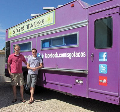 Beau Mills, left, and Tyson Brown stand in front of their big purple taco truck. <BR>KIM STEELE/Miner