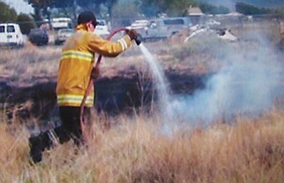 A firefighter with Northern Arizona Consolidated Fire District 1 helps extinguish a brushfire in April on Northern Avenue. Officials believe the blaze was the one in a string of roadside arson fires in Kingman.<BR>Courtesy