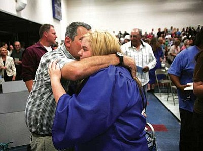 RODNEY HAAS/Miner<br /><br /><!-- 1upcrlf2 -->Kent Roggero hugs his daughter Krista on Wednesday after graduation ceremonies at Kingman Academy of Learning High School. Krista survived thyroid cancer surgery in her junior year.