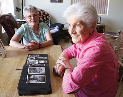 Genny Lucas, left, listens as her friend and co-worker Ginette Walker talks about her dangerous life in France during World War II and shows photographs from that time.<BR>JC AMBERLYN/ Miner
