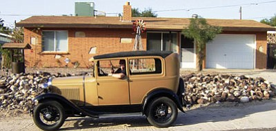 Courtesy<BR> Keith Ferguson sits in a friend's Model A antique car in front of his Bullhead City house.