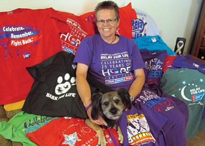 KIM STEELE/Miner<BR> Joleen Goss and her dog Dusty sit among some of the colorful Relay for Life T-shirts Goss has worn over the years for the annual event in Kingman. Goss was diagnosed with ovarian cancer in 2001 and has been instrumental in organizing and promoting the local Relay for Life. She will be telling her story in September to a congressional committee in Washington, D.C.