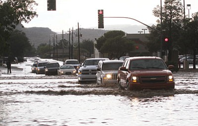 JC AMBERLYN/Miner<BR>Traffic sloshes through the flooded intersection of Stockton Hill Road and Detroit Avenue Saturday afternoon.
