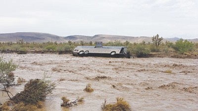 A tour bus was swept away by a flash flood that crossed Piece Ferry Road on Sunday. The 33 passengers, tour guide and driver escaped injury. (Courtesy)