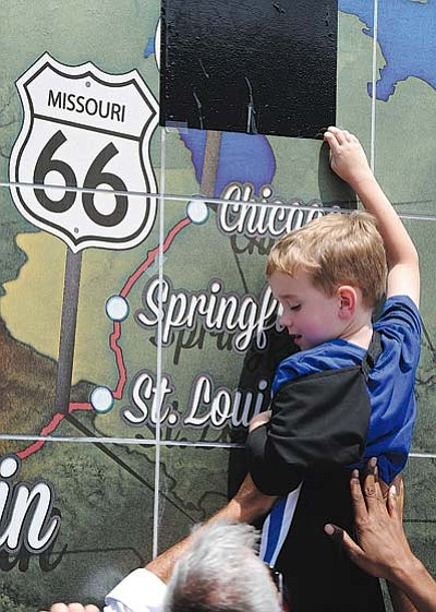 T. ROB BROWN/Joplin Globe<BR> Four-year-old Bryson Snider of Clinton, Okla., gets a boost up to unveil the last state Route 66 sign from Paul Whitehill, owner of Images in Tile which created the murals, during the opening celebration Friday afternoon for the Route 66 International Festival in Joplin, Mo.