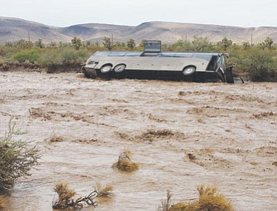No one was injured when this tour bus was caught in floodwaters. The driver faces a reckless driving charge. (Courtesy)