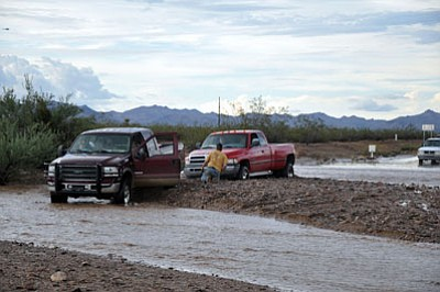 BUTCH MERIWETHER/Courtesy<BR> A Golden Valley resident hooks a chain to a hook up to a Dodge pickup that got stuck when the driver attempted to drive through a flooded area of Estrella Road. It is estimated that more than 30 vehicles got stuck attempting to cross various flooded roads during a recent storm that hit Golden Valley.