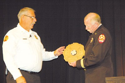 JOANNA DODDER/Courier<BR> Kingman Assistant Fire Chief Keith Eaton, left, presents Arizona State Fire School Training Committee Chair Bob Hansen with a plaque commemorating the Doxol explosion, to benefit the school's auction. The plaque features metal from the railroad tank that exploded in the 1973 disaster.