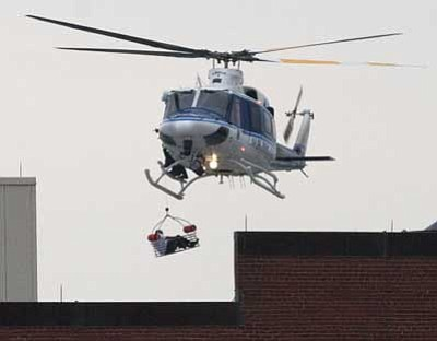 Jacquelyn Martin/The Associated Press<br /><br /><!-- 1upcrlf2 -->A U.S. Park Police helicopter removes a man in a basket from the Washington Navy Yard this morning. Earlier, the U.S. Navy said it was searching for an active shooter at the Naval Sea Systems Command headquarters, where about 3,000 people work.