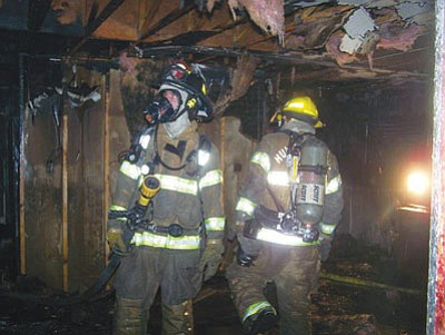 Firefighters from the Northern Arizona Consolidated Fire District inspect a house that burned Wednesday night on Butler Avenue. The blaze is considered suspicious. (Courtesy)